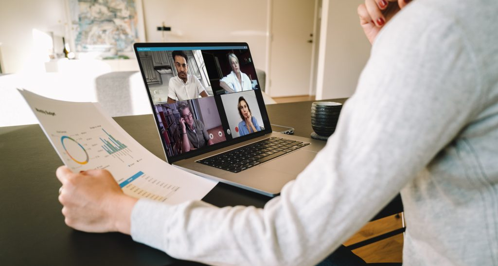 Group of businessmen and businesswomen smart working from home. View from side of woman talking to her colleagues about business plan over a video conference.
